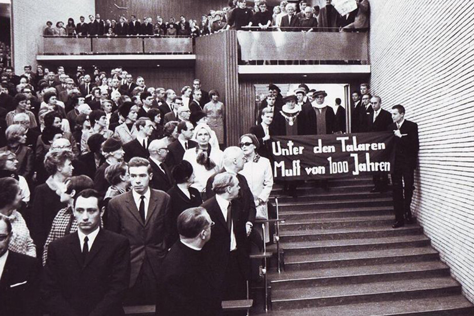 "Standing room only! Audimax on 9 November 1967. Two students carry a banner bearing the words: ""Under these robes—1,000 years of rot!"""