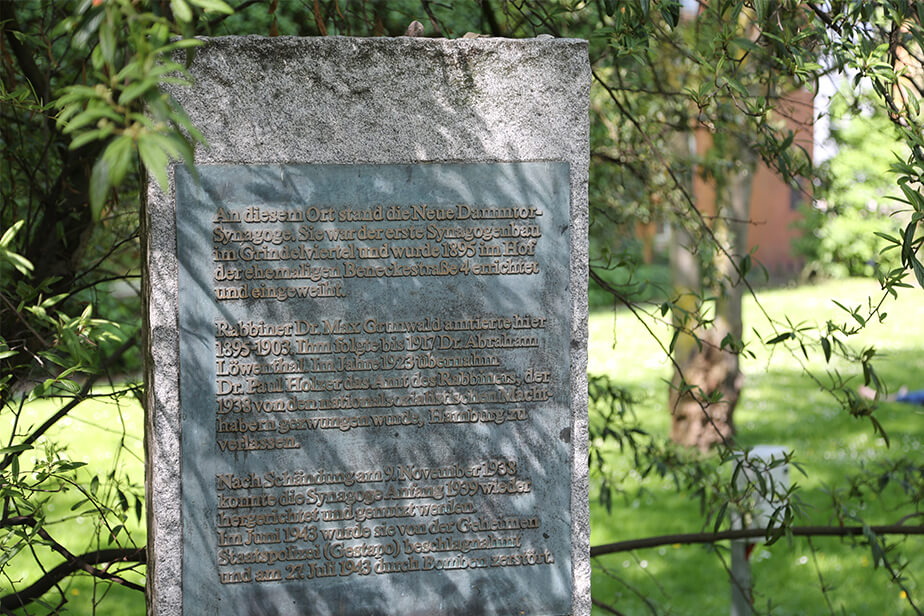 The photo shows the memorial to the New Dammtor Synagogue. It is an upright stone slab with an inscribed metal surface.